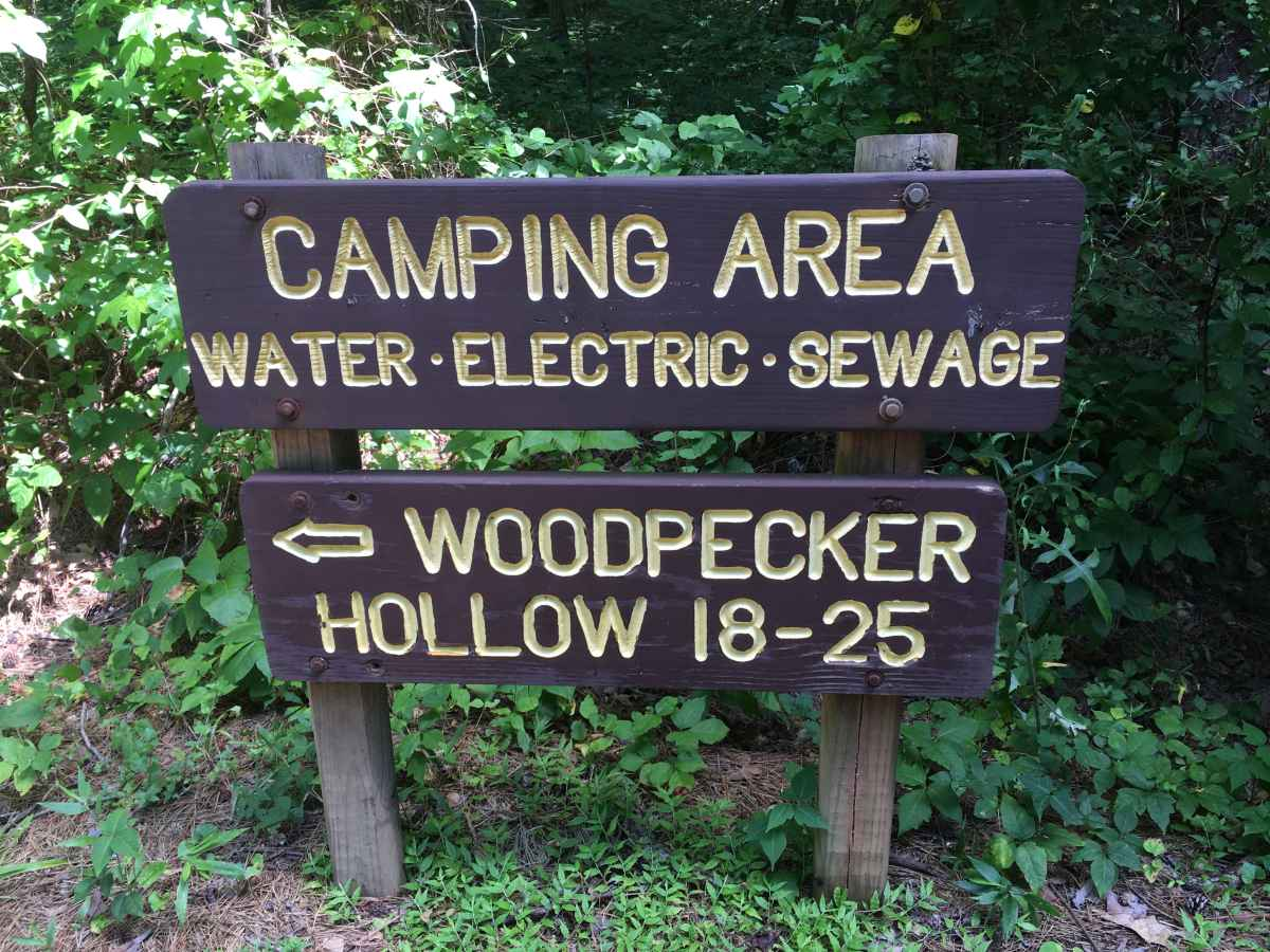 The sign for the Woodpecker Hollow Camping Area, full hookup campsites.