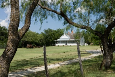 Farmhouse framed by mesquite trees and barbed wire fence.