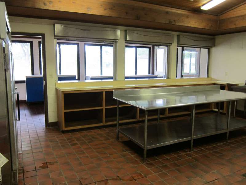 Lots of shelves, prep area, a commercial refrigerator, and serving area.