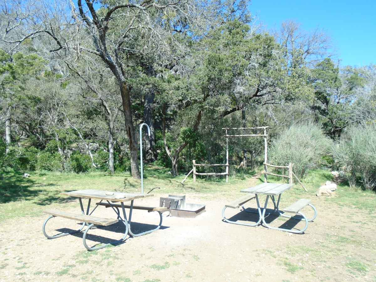 There are three picnic tables, a fire ring and a lantern post.