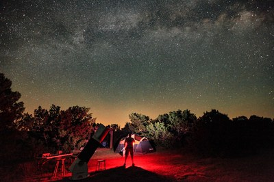 Person standing at campsite observing night sky