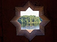 View of lake through eight-pointed star in wall of combination buildin