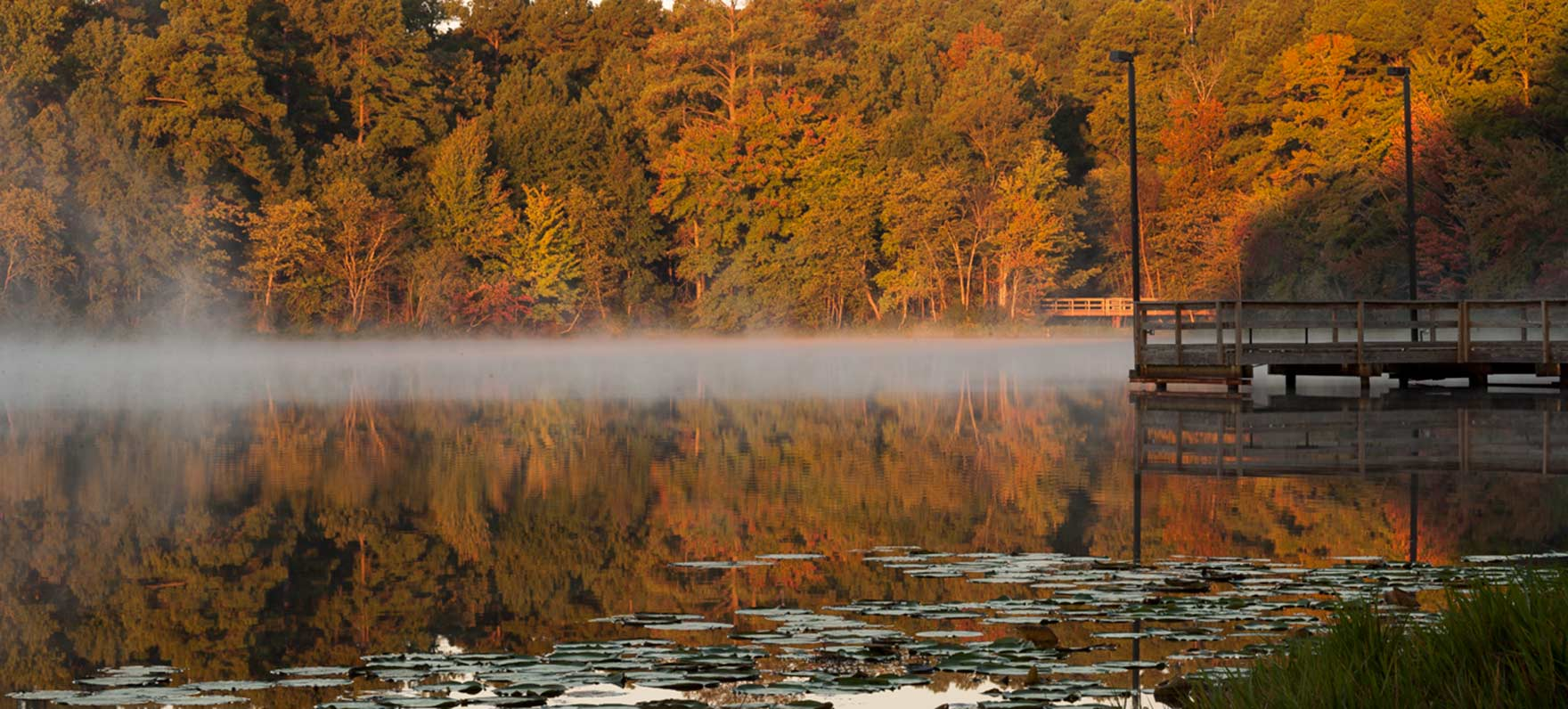 View of lake and fishing pier with colorful fall foliage
