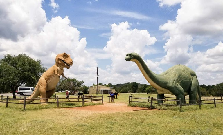 Two dinosaur sculptures at Dinosaur Valley, with a person standing between them for scale.