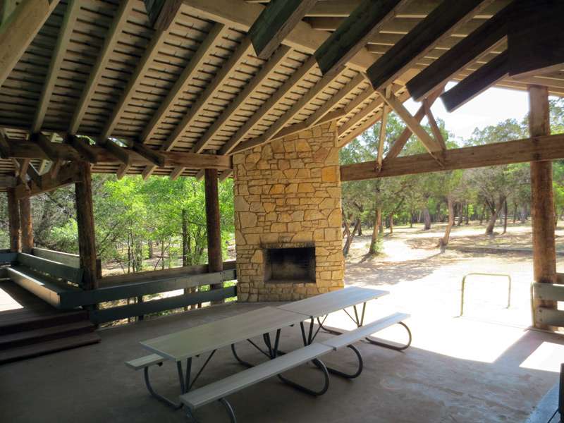The pavilion has picnic tables and a fireplace.