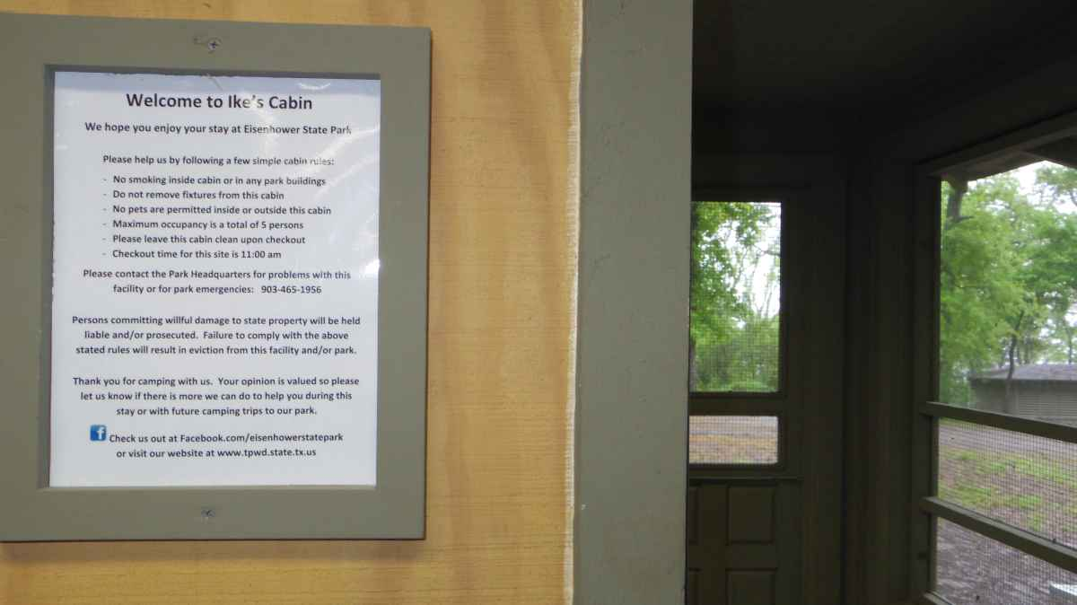 Inside the Cabin looking at the screened porch and the posted cabin rules.
