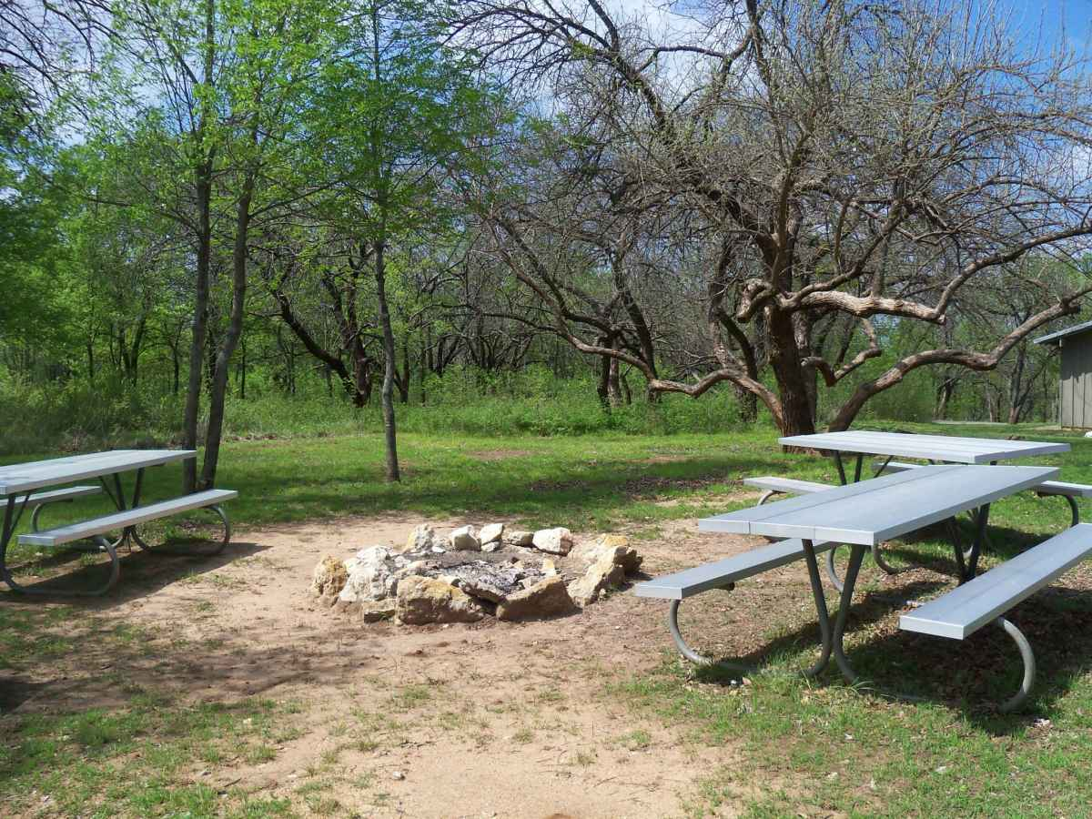 There is a large firepit with surrounding picnic tables next to the Rec. Hall.