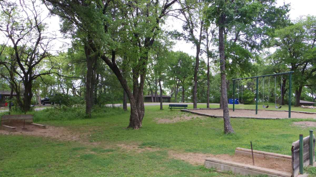This playground and the Screened Shelter Area is behind the Rec. Hall.