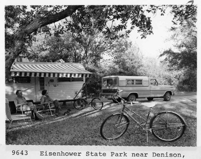 "historical photo of folks sitting in front of camper, ca 1950s. At bottom, it says ""Eisenhower State Park near Denison."""