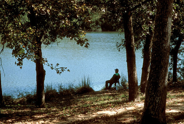 Man sitting in chair by the lake holding a fishing pole