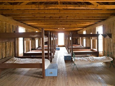 Bunk beds lined up in a large hall with storage chests at the foot of some beds.