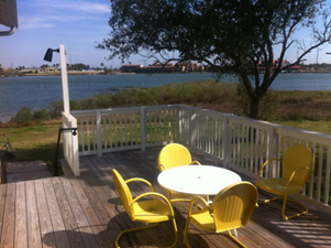 The deck has a table, chairs, light, and a great view of the lake.