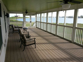 The screened porch has chairs, lights, ceiling fans, and a great view of the lake.