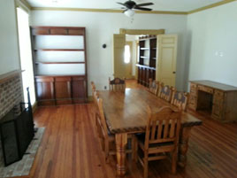 A view of the dining room, which has a fireplace, ceiling fan, and a dining table with 8 chairs.