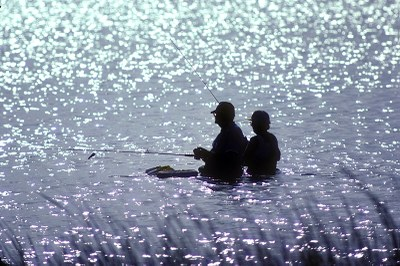 Two anglers wading in waist-high water