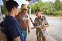 Volunteer in uniform giving park information to a father and son