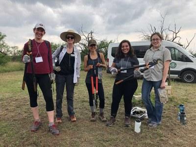 Women volunteers holding landscape tools