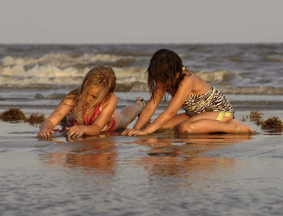 Girls playing in sand Galveston Island State Park
