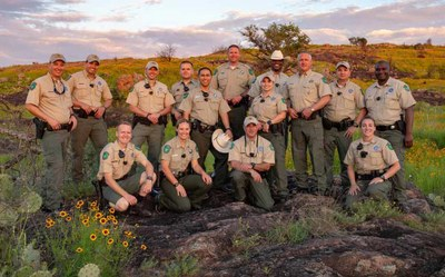 Diverse group of state park police officers posing in nature at Inks Lake State Park