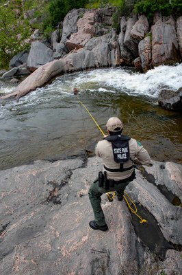 Officer holding a rope attached to a person in rough water.