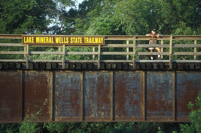 "Man standing on trailway bridge with sign on bridge that says ""Lake Mineral Wells State Trailway"""
