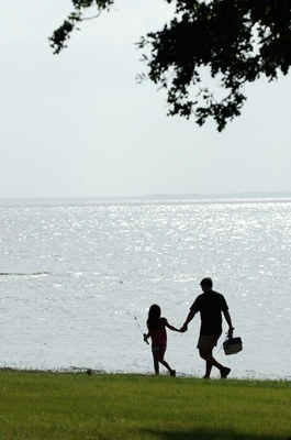 Silhouette of father and daughter by lake carrying fishing gear