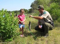 Park ranger holds line with fish as little girl holds fishing pole
