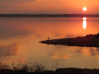 Sunset over Lake Whitney, with a bird standing on shore