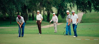 Golfers standing on course watching another golfer putt.