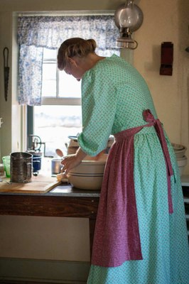 Woman in period clothing kneading bread