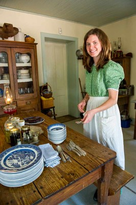 Woman in period clothing standing in the kitchen