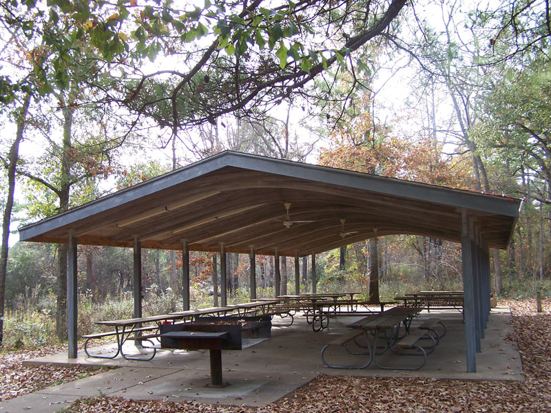 The Group Pavilion has picnic tables, a cooking grill, electricity, lights, ceiling fans, and water.