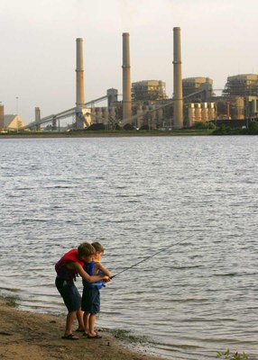 Two kids fishing on shore of lake with power plant across the water