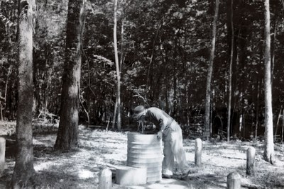 Man drinking from historic concrete drinking fountain in the woods