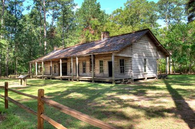 log cabin with split -rail fence in front.