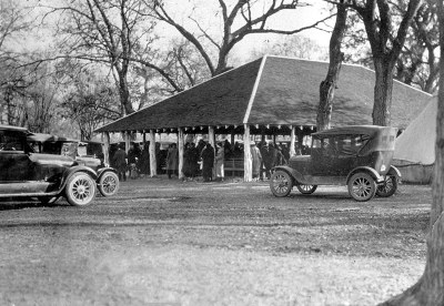 Black & white photo of pavillion with old cars parked in front.