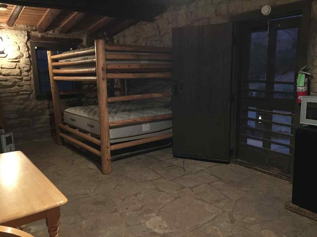 Inside Cow Camp Cabin #1. A view of the bunk bed, microwave, refrigerator, table, A/C unit and front door.
