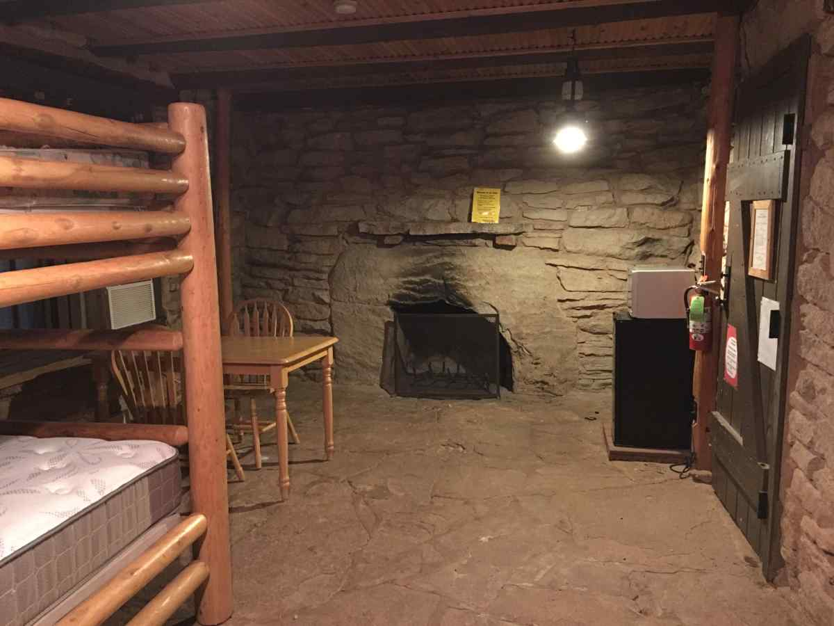 Inside Cow Camp Cabin #3. A view of the fireplace, table, mini-refrigerator, microwave, and bunk beds.