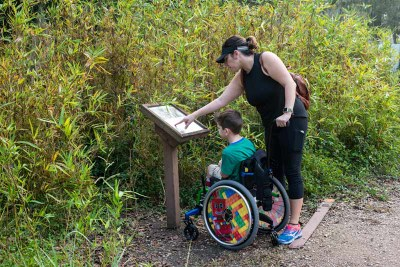 Boy and mom looking at sign by trail at Brazos Bend State Park