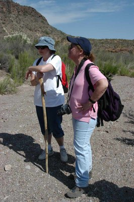 Two women pausing on a hike, wearing hats and hiking boots.