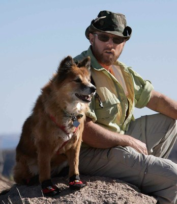 Hiker and his dog sitting on a rock. Dog is wearing booties