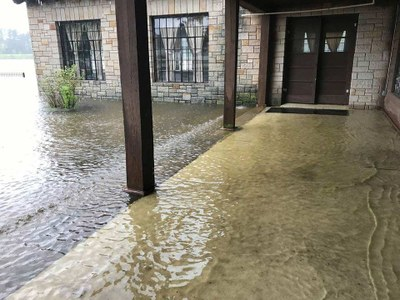 Water covering the porch of park building