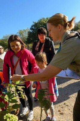 Female park ranger showing child and parent a leaf on a shrub.