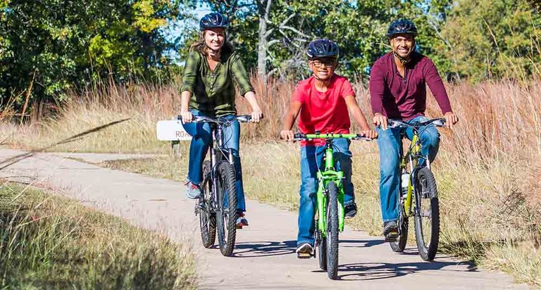 Diverse family riding bicycles on a paved road in a Texas state park.