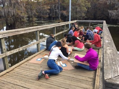 Group of people painting on a fishing pier over a lake.