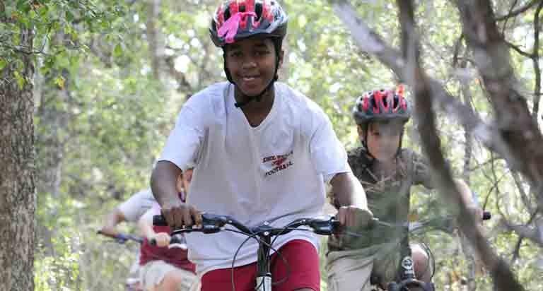 Boys riding mountain bikes wearing helmets in McKinney Falls State Park.