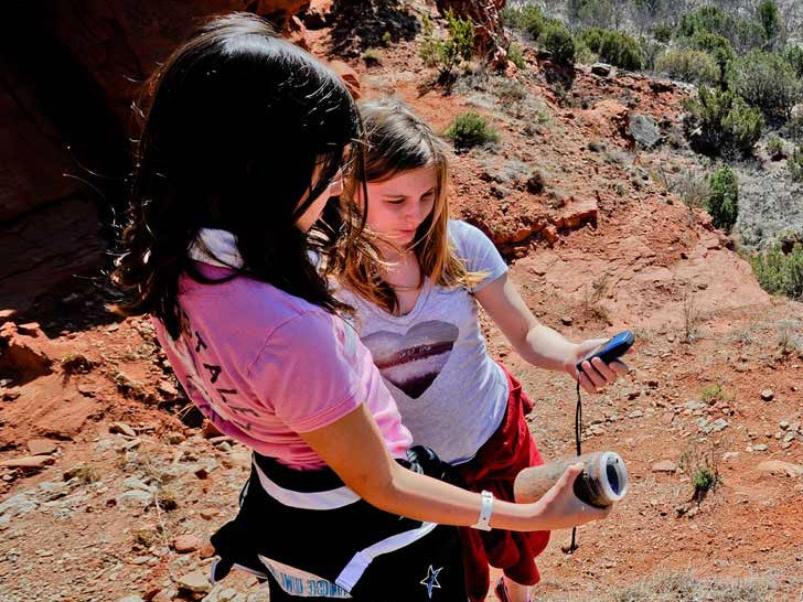 Two girls check out the geocache they found
