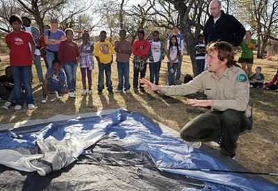 Park ranger shows families how to set up tent