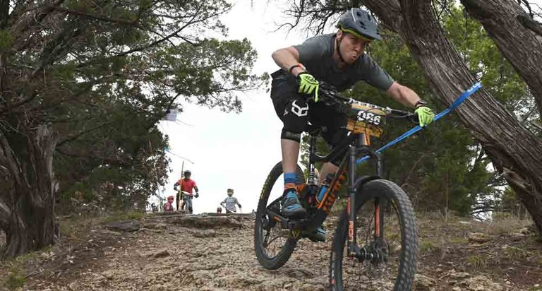 Man riding mountain bike down a hill at Dinosaur Valley State Park