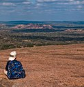 Boy sitting on top of Enchanted Rock looking out at view.